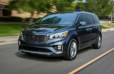 2019 Kia Sedona exterior front fascia and drivers side going fast on road with trees