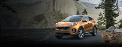 Burnished Copper 2018 Kia Sportage exterior front fascia and drivers side on road next to pine tree