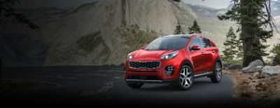 Hyper Red 2018 Kia Sportage exterior front fascia and drivers side on road next to pine tree