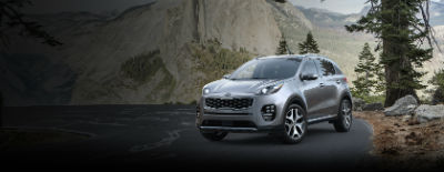 Mineral Silver 2018 Kia Sportage exterior front fascia and drivers side on road next to pine tree