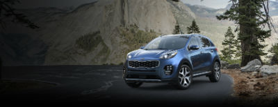 Pacific Blue 2018 Kia Sportage exterior front fascia and drivers side on road next to pine tree