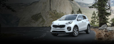 Snowy-White Pearl 2018 Kia Sportage exterior front fascia and drivers side on road next to pine tree