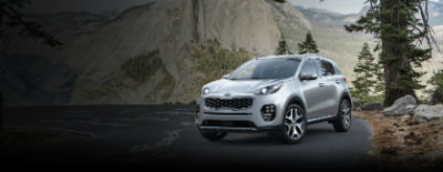 Sparkling Silver 2018 Kia Sportage exterior front fascia and drivers side on road next to pine tree