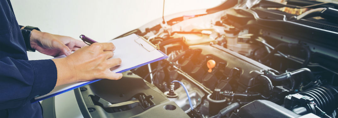 mechanic holding clipboard over engine of car