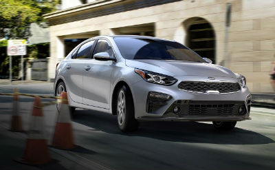 2019 Kia Forte exterior front fascia and passenger side on road with traffic cones blurred