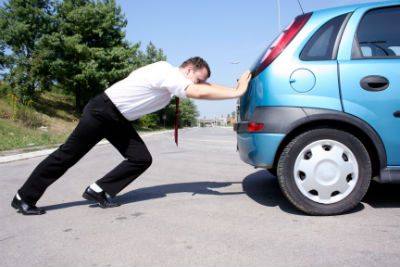 Businessman pushing his car in parking lot