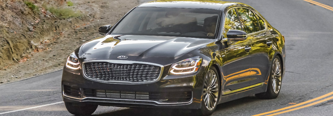 2019 Kia K900 in black rounding a curve in the road