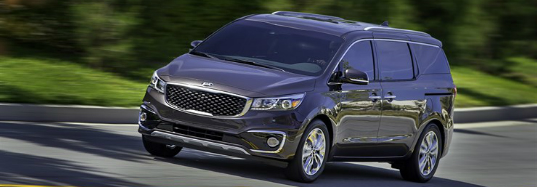 2017 Kia Sedona driving down an empty street
