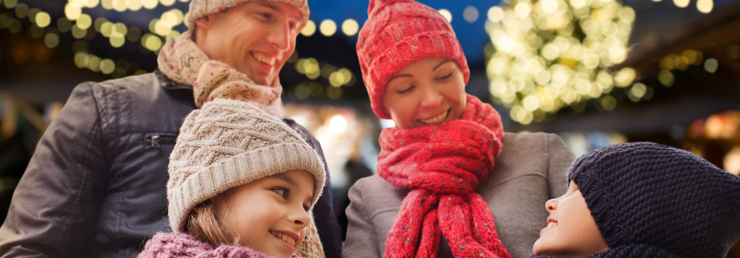 Family in hats and scarves smiling near Christmas lights