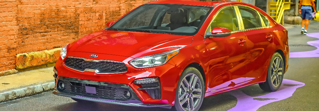 Red 2019 Kia Forte parked in front of a brick wall