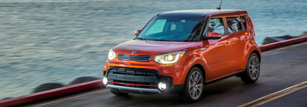 2019 Kia Soul in orange driving near the water