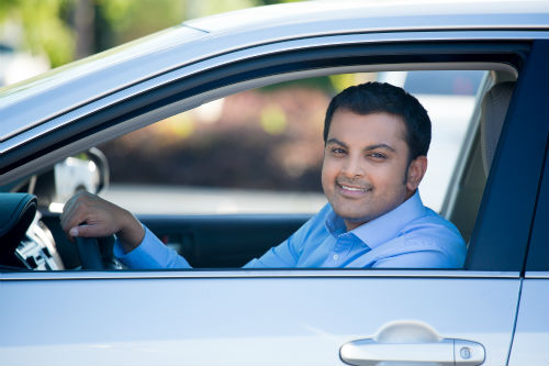 Man smiling while sitting in a car