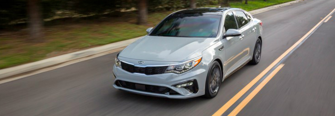 2019 Kia Optima in grey driving on a tree lined street