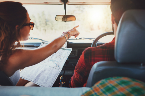 Couple in the car looking at a map while driving