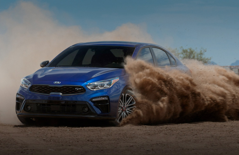 2020 Kia Forte in blue kicking up sand