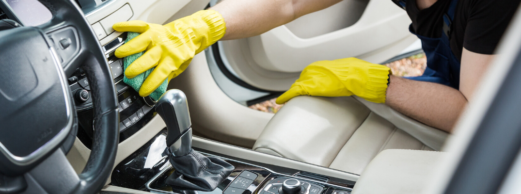 Closeup of male hands cleaning the radio of a vehicle with yellow gloves
