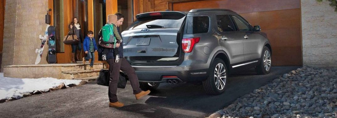 Man holding a child opening the trunk of a 2018 Ford Explorer using his foot