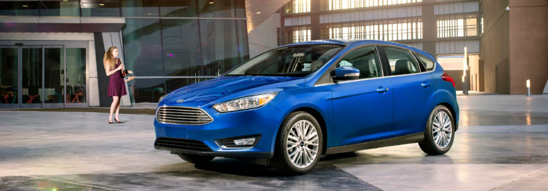 2018 Ford Focus hatchback exterior front fascia and drivers side with woman standing off to side
