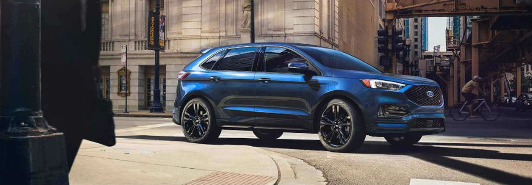 2019 Ford Edge exterior front fascia and passenger side on city road with person biking
