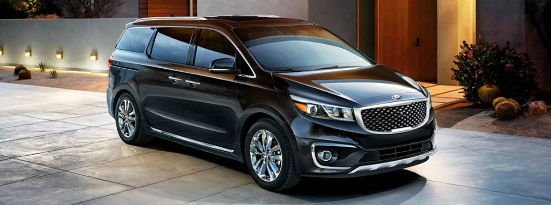 Black 2018 Kia Sedona parked outside of upscale residence