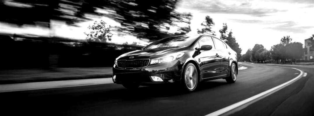 Black and white image of 2018 Kia Forte cruising on a highway