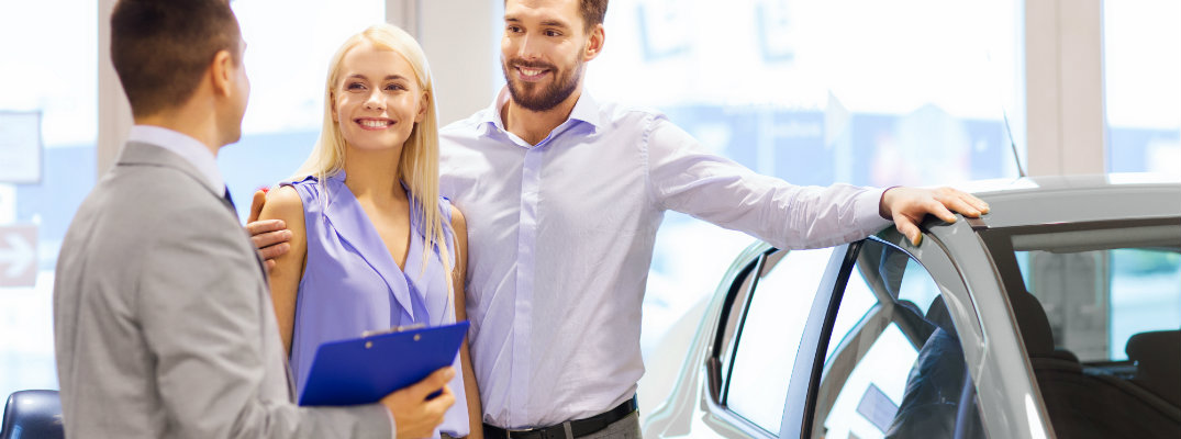 Couple at a dealership and talking with a sales professional