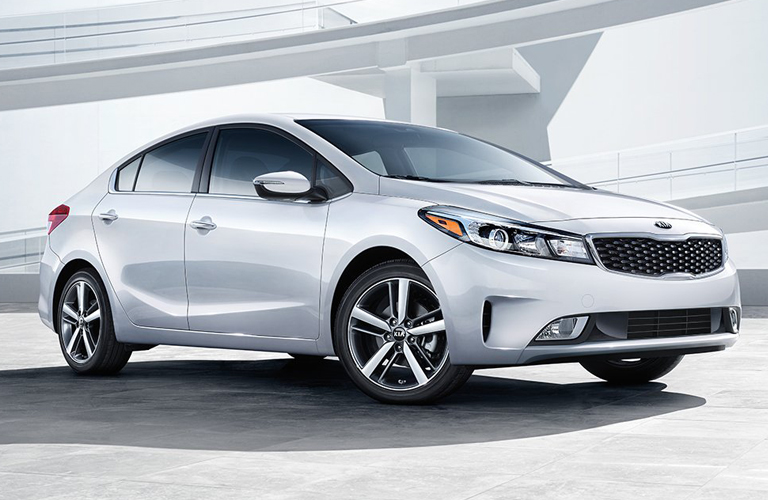 Exterior view of a silver 2018 Kia Forte parked under an overpass
