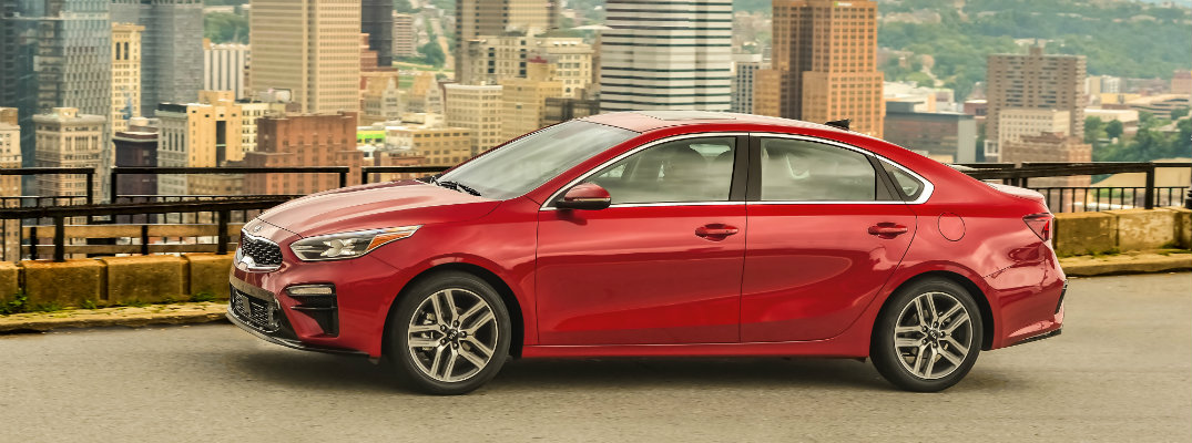 Red 2019 Kia Forte driving through a city
