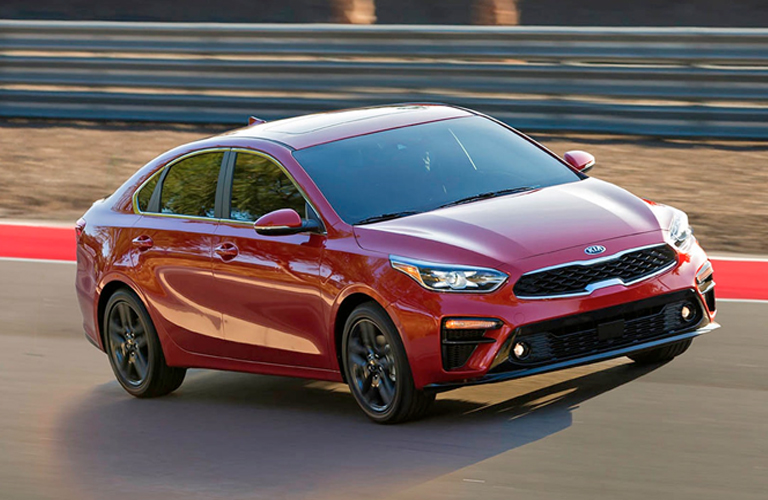Exterior view of a red 2019 Kia Forte driving down a closed racetrack