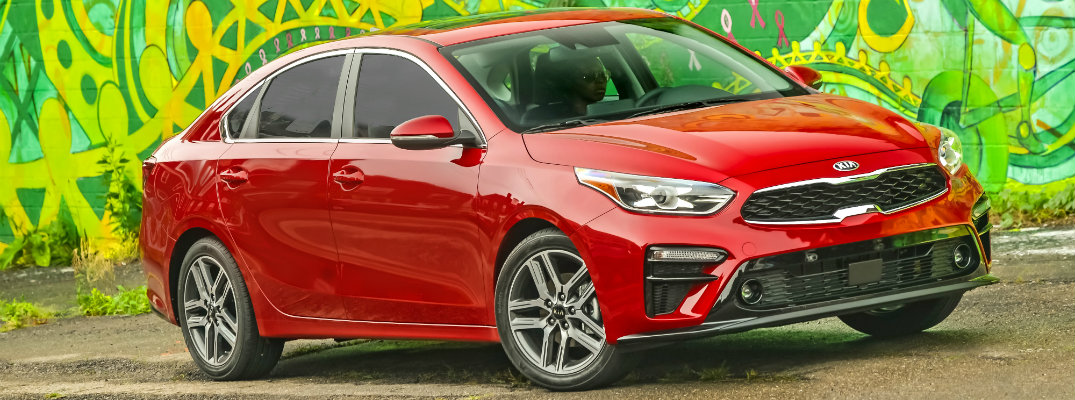 Red 2019 Kia Forte parked in front of graffiti-covered wall