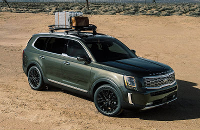 2020 Kia Telluride exterior front fascia and passenger side on sandy space with fence in background