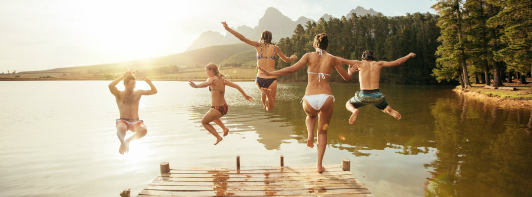 Group of friends jumping in a lake