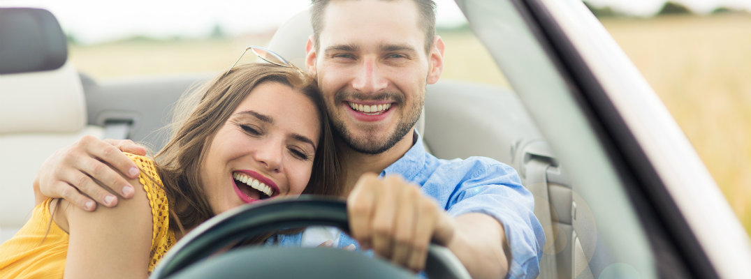 Couple behind the steering wheel of a car