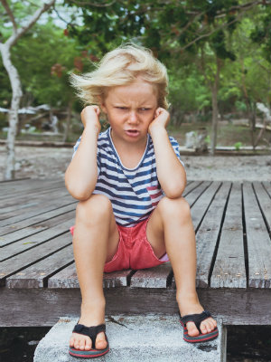 Little blonde girl acting cranky on a porch