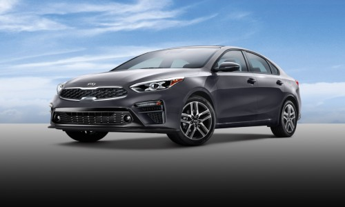 2020 Kia Forte exterior grey paint facing left showing front bumper and driver side doors on grey ground with sky_o