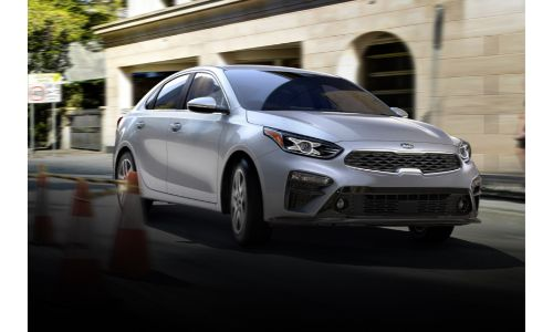 2020 Kia Forte driving downhill grey paint showing front and some of passenger doors