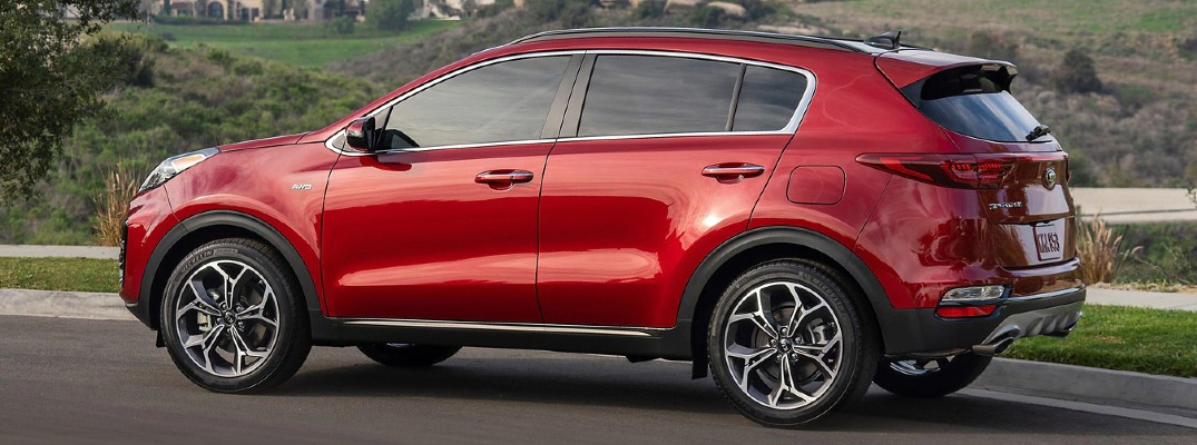 2020 Kia Sportage Red paint driving down road trails in background