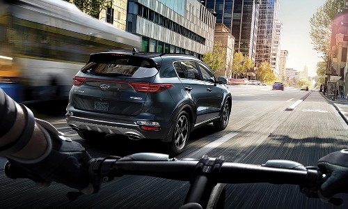 2020 Kia Sportage driving through city seen by bike cyclist