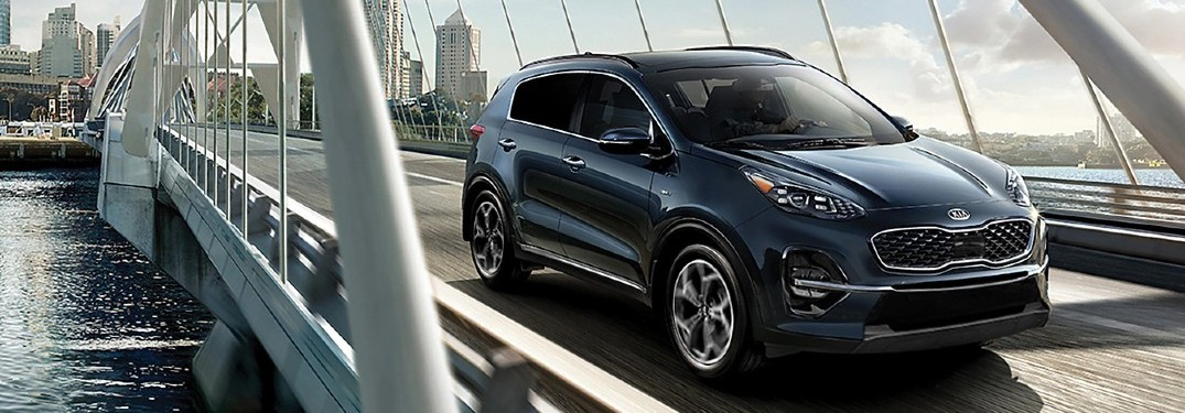 2020 Kia Sportage grey driving on bridge over river