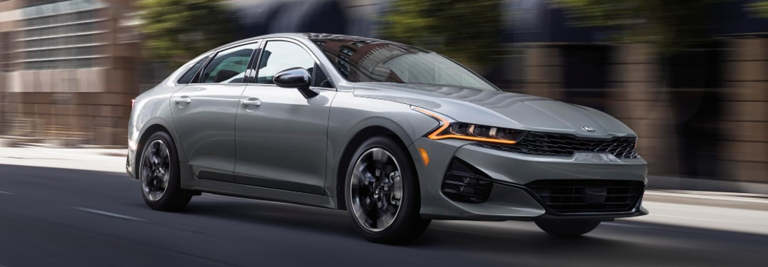2021 Kia K5 grey driving in city with motion blur showing passenger side of car