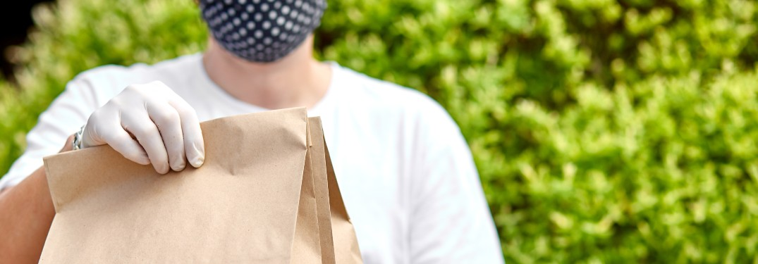 stock photo of man handing paper bags as delivery with mask and gloves