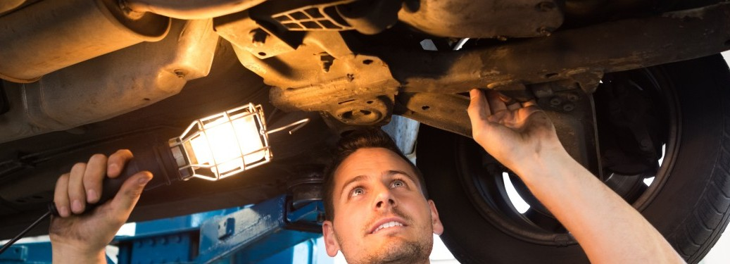 mechanic looking under vehicle with work light