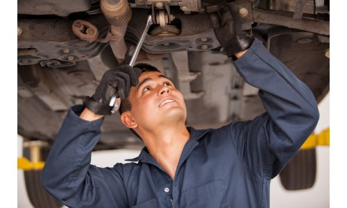 mechanic with wrench working on underside of car