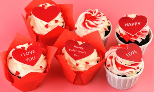 six valentine cupcakes with paper hearts