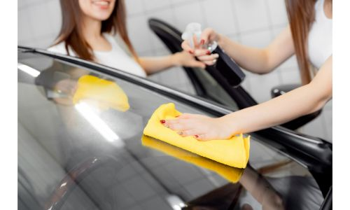 women cleaning inside and out of windshield with yellow cloth