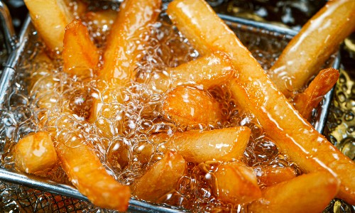 french fries frying in oil with basket