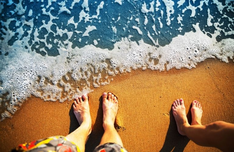 Male and female barefoot on the beach