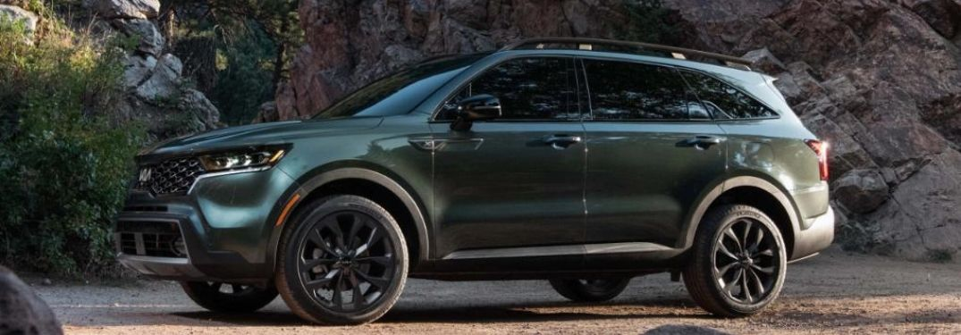 2022 Kia Sorento Green parked in the forest with rocks on background