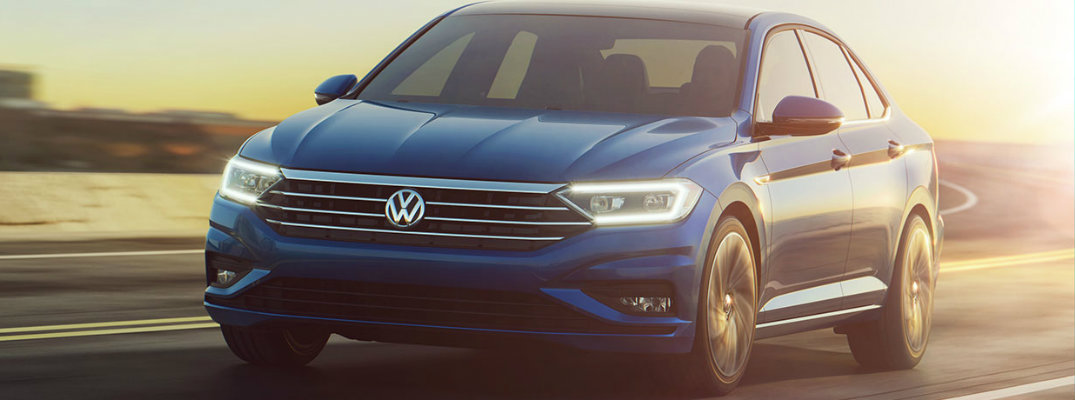 Front view of blue 2019 Volkswagen Jetta driving on winding highway road at dusk