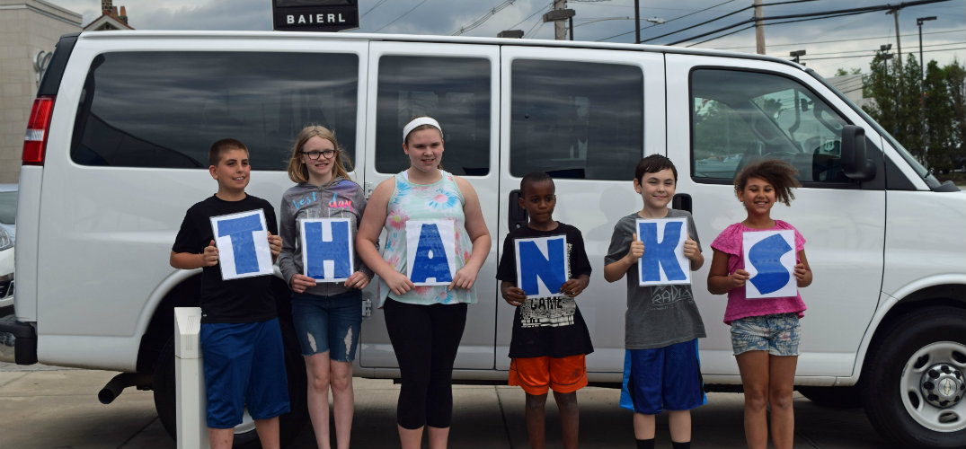 kids holding thanks sign in front of van